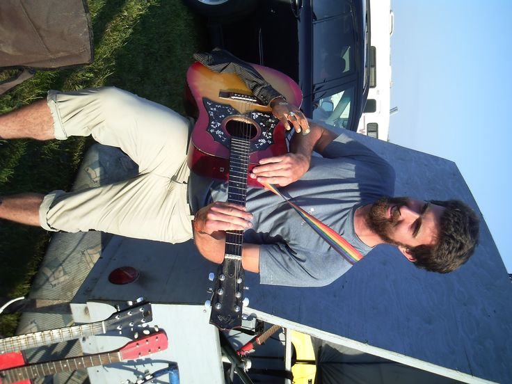 Folk Fest fan who has seen Lorne in past years stops by to check out his guitars and strums some tunes