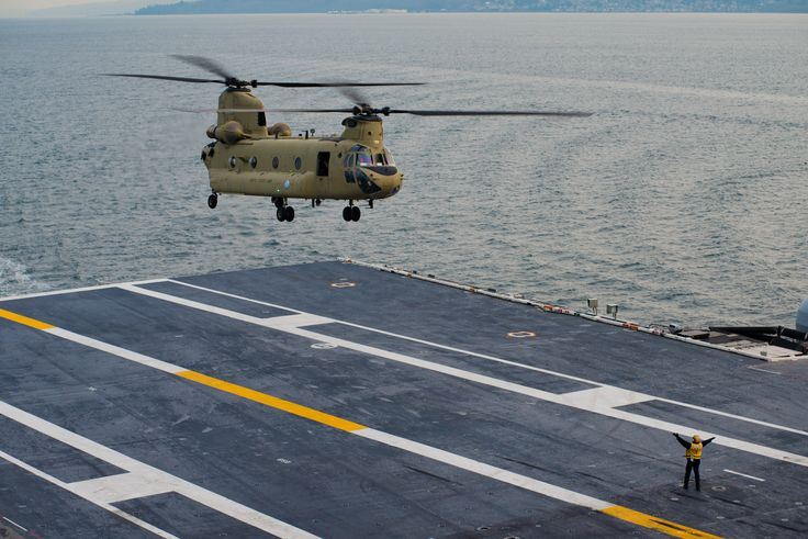 PUGET SOUND (Dec. 18, 2016) A Sailor directs a CH-47 Chinook assigned to the Washington National Guard for landing aboard the aircraft carrier USS John C. Stennis (CVN 74) during deck landing qualifications. Deck landing qualifications allow helicopter pilots to gain proficiency landing onboard ships. John C. Stennis is underway to conduct routine training in the 3rd Fleet area of responsibility. (U.S. Navy photo by Petty Officer 2nd Class Jackson G. Brown/Released)