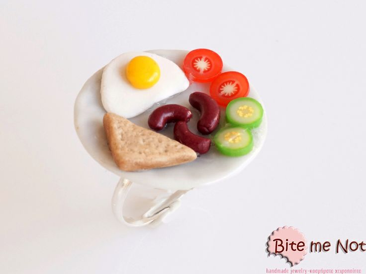 English breakfast Round ceramic plate with egg,toast bread,tomatoes,cucumbers and mini sausages on a silver plated adjustable ring base.