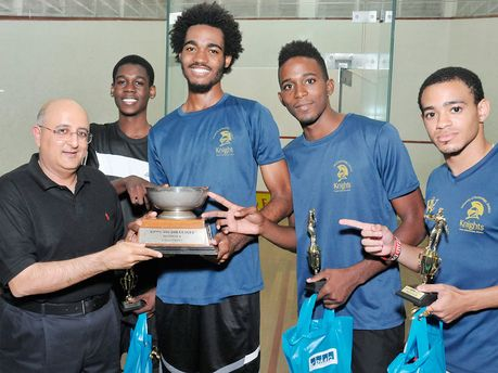 Tarun Handa (left), managing partner for KPMG in Jamaica, presents the championship trophy to the UTech Knights, who won the KPMG Squash Lea...