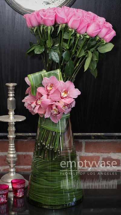 Side cluster of pink roses and pink cymbidium orchids, in a vase filled with swirls of steel grass and hints of flax leaf.