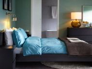 Black-brown bed, bedside table, chest of drawers and white/light blue bedlinen