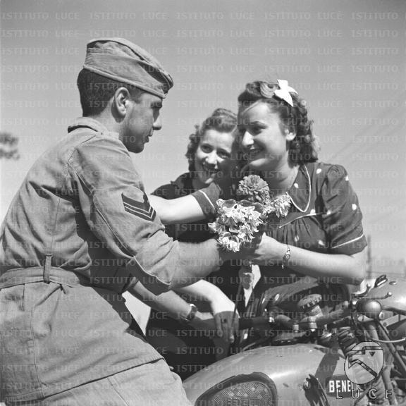 Due ragazze offrono dei fiori a un volontario della G.I.L. alla guida di una motocicletta Benelli  RG/RG108/RG00004334.JPG