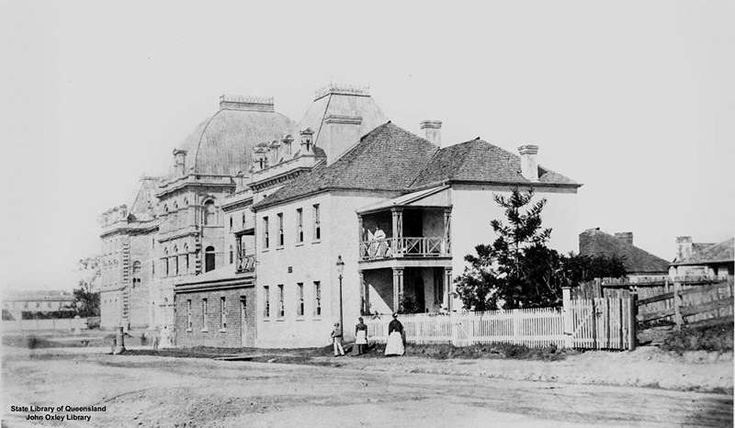 Parliament House and the first Bellevue Hotel (1865) in George Street, Brisbane. Staff? pose in front of the hotel. The facades of the hotel and Parliament House featured. A young pine stands in the hotel garden.