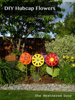 The Weathered Door: Hubcap Flower Yard Art I need to do this in my garden this summer!