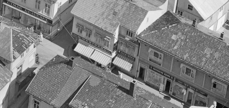 Flott detaljutsnitt fra Tønsberg torg og Storgaten i 1953. Butikkskiltene viser navn som Otmar Gravdahl, O. Westberg, Brødrene Bjune og L.L.Holt. Se flere skilt og mer av hva som røte seg mellom hustakene denne 1953-dagen i den store originalen:  https://www.flickr.com/photos/vestfoldmuseene/14424495980/sizes/o/