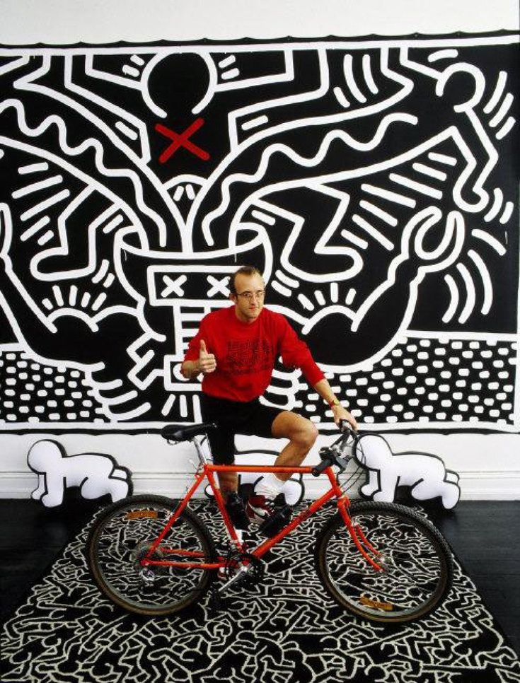"""Thomas Hoepker, USA. New York City. 1986. Graffiti artist Keith Haring.  In 1986 he photographed a young Keith Haring in front of one of his graffiti-inspired artwork; Hoepker perfectly captures Haring's downtown persona, with the artist's red bike parked on top of a rug bearing his work as small sculptures """"crawl"""" in the background."""