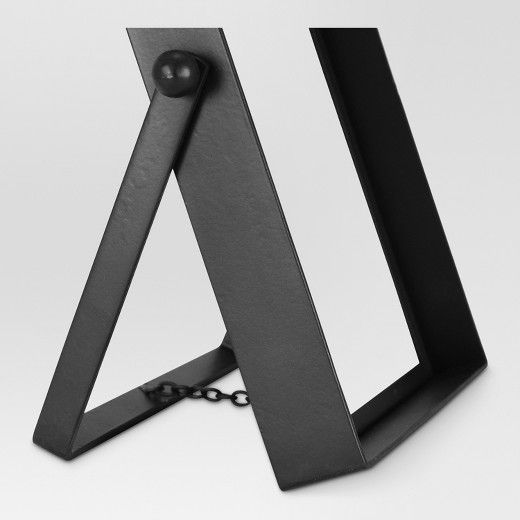 Bring a pop of contemporary style to your home or apartment with this Single Image Frame from Threshold™. This black metal picture frame features a unique pivot easel design for a pop of easy, bold style. Use this picture frame to protect and display your most cherished memories around your home. Place this contemporary picture frame with simple and classic black design on a shelf, end table or mantel for a great decorative accent piece.