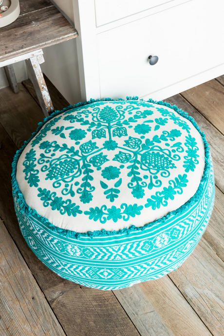 The Turquoise Embroidered Floor Pouf is a beautiful textile that features intricate embroidery, 100% cotton fabric, and bright turquoise color.