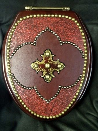 """BEAUTIFUL and LUXURIOUS custom toilet seat, The perimeter is done in French natural tacking and the top and bottom with INDIVIDUALLY PLACED """"Old Gold"""" tacking Shown in a high quality RED """"crackle embossed"""" and smooth coordinating burgandy leather , on a MAHOGANY wood seat with a piano finish. Then accented with a metal cut out, Read more..."""