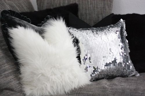 Black fur pillows, white fur pillows, silver sequined pillow.
