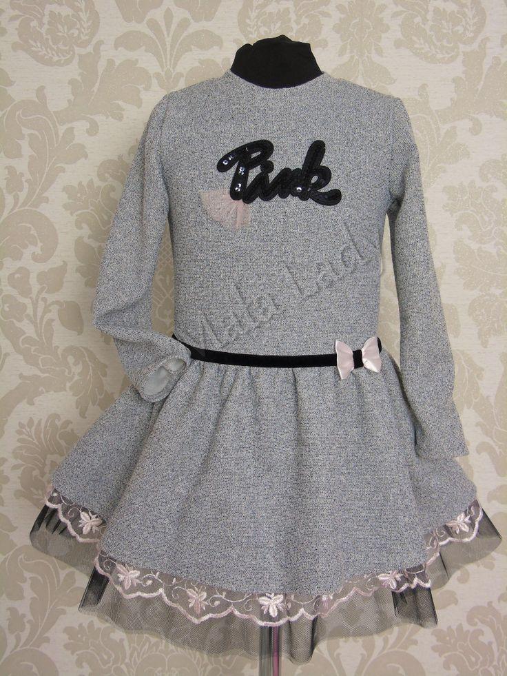 Bajeczna sukienka Pink w odcieniu szarości, delikatnie rozkloszowana. Dół sukienki to połączenie materiału bawełnianego z tiulem oraz koronką, odszyty podszewką. Sukienka posiada długi rękaw oraz kryty zamek z tyłu kreacji. Przód sukienki ozdabia czarny pasek z beżową kokardą.  Sukienka dostępna z dodatkami w kolorze różu lub czerwieni.