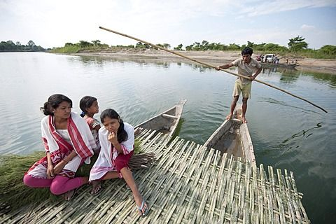 Young girls wearing traditional Assamese gamosa scarves, on simple ferry being poled across the Brahmaputra river, Assam, India, Asia