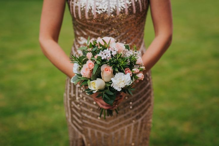 Pinky pastels, ivory and green look fab against these glittering bridesmaid dresses. Photo by Benjamin Stuart Photography #weddingphotography #weddingflowers #bridesmaid #goldwedding #pinkandivory #handtiedbouquet
