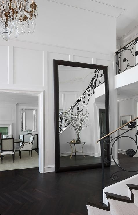 Modern two story foyer with a crystal chandelier features paneled walls lined with a black framed floor mirror atop the dark herringbone floors.