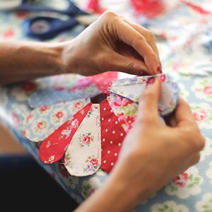 Someone at a Cath Kidston workshop sewing a dresden plate pattern with paper templates in true EPP style.
