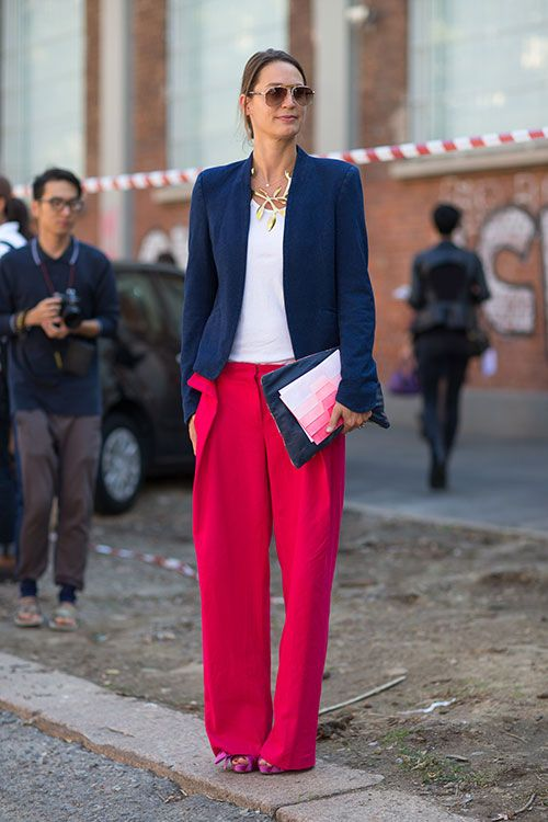 Milan Fashion Week spring 2014, Street style. White top, blue blazer, wide flared red pants, golden statement necklace pink and black clutches.