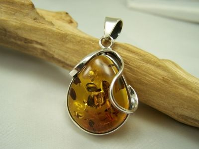 Beautiful honey colour amber pendant with drop shape amber in sterling silver modern frame.