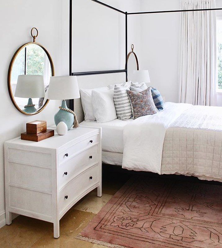 Round mirror in bedroom, white dresser, white nightstand, black and grey headboard, neutral bedroom, coral rug bedroom