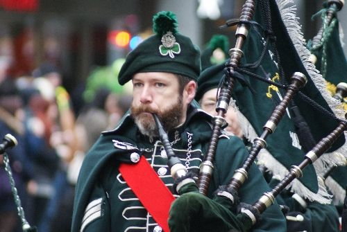 A bagpiper marching in the annual Vancouver St. Patrick's Day Parade.