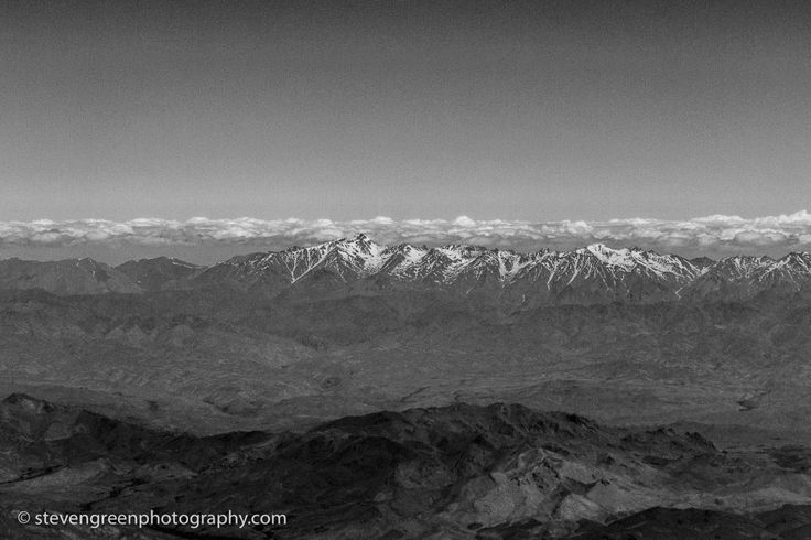 Snowy Peaks and Cloud Layer - Monochrome aerial photograph of snow-capped mountain peaks and distant cloud layer above a remote region of Afghanistan near the Hindu Kush #Central Asia #Hindu Kush #Steven Green #aerial photography #afghanistan #blackandwhite #capped #clouds #elevation #landsbelow #landscape #layer #monochrome #mountains #photography #snow #snow-capped #travel