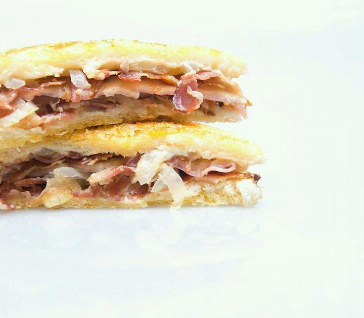 Sándwich de bacon sobre capa de cebolla caramelizada y queso con salsa preparada  a base de mahonesa, mostaza y salsa inglesa  (Jose Tandem)
