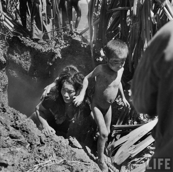 Frightened civilian woman and children emerging from cave where they had hidden during battle between Japanese & American forces for control of Saipan. Description from pinterest.com. I searched for this on bing.com/images