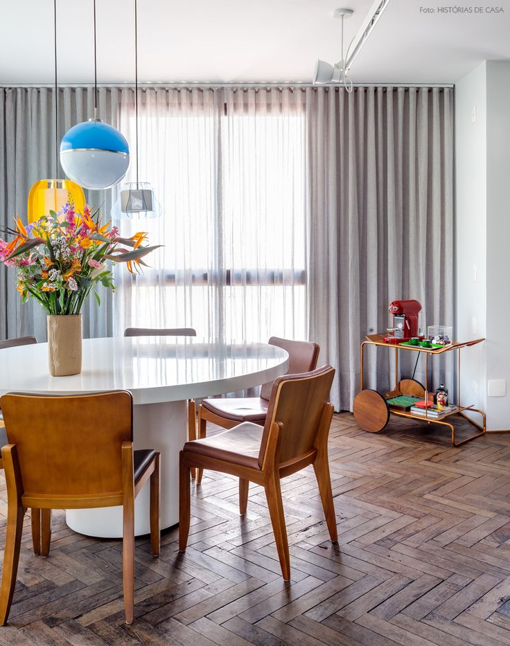 sala de jantar com pendentes vintage, cortinas cinza e piso de madeira rústica