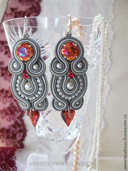 Серьги `Стрела Купидона`. Изысканные серьги, выполненные в технике сутажной вышивки, в которых просматривается очень красивый переход цвета кристаллов от огненного оттенка Astral к ярко-красному Siam и, наконец, к глубокому красному цвету Magma в подвесках-сердечках.