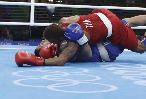 Thailand's Amnat Ruenroeng, top, and Argentina's Perrin Ignacio fall during a men's lightweight 60-kg preliminary boxing match at the 2016 Summer Olympics in Rio de Janeiro, Brazil, Sunday, Aug. 7, 2016. (AP Photo/Frank Franklin II)