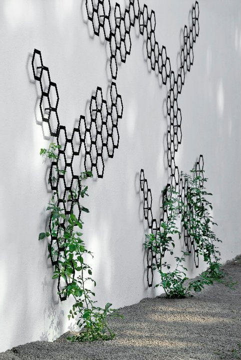 Garden trellis as art. It could be fun to commission some pieces of art trellis that could be used to train vines up to a screen/trellis added to top of wall.