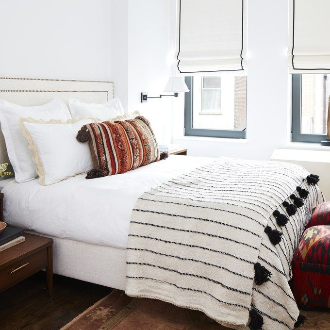 Minday Kaling's Master Bedroom, white paint color, upholstered headboard, black & white bedding, textile ottomans,  roman shades, wood floors, area rug, swing arm lamps