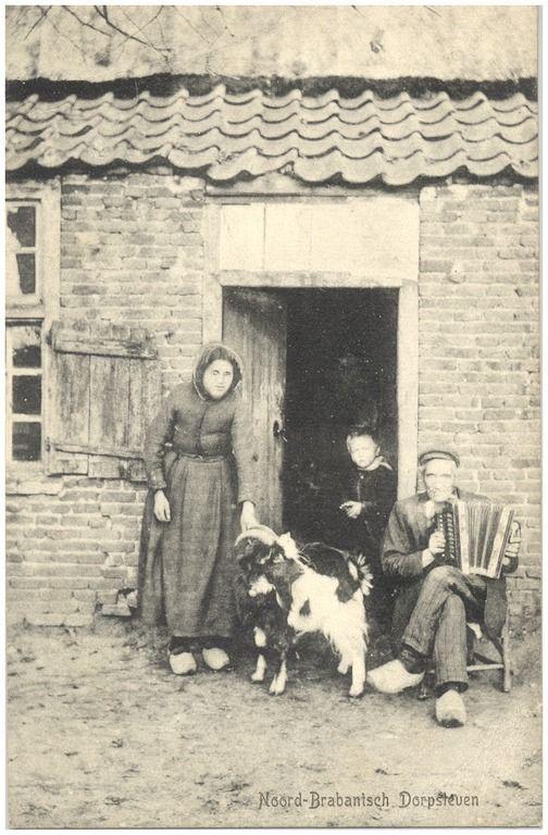 Het spelen van accordeon, met in de deuropening ernaast een geit, een vrouw en kind #Brabant