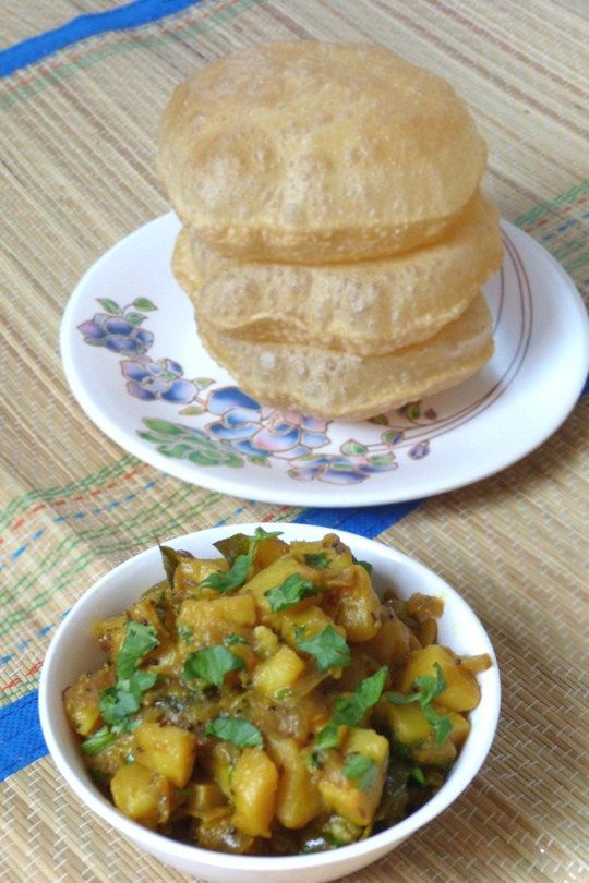 Poori Bhaji Recipe - Aloo Puri Recipe • Oil – 2 tablespoons • Mustard seeds – ½ teaspoon • Cumin seeds – ½ teaspoon • Green chilies – 3-4, chopped finely • Curry leaves – 6-7 • Onion – 1 cup, cubed • Potatoes – 2 cups • Water – ½ cup • Turmeric powder – ½ teaspoon • Lemon juice – ½ teaspoon or to taste • Salt – to taste • Cilantro – few sprigs, chopped finely for garnishing. Instructions Make Poori – Click here for detail ingredients and recipe for poori