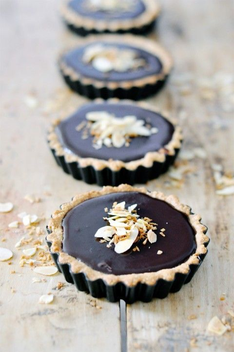 Coconut + Chocolate Tart (vegan,gluten-free) OMG! FOR THE CRUST ½ cup unsweetened shredded coconut 1 ½ cups almond flour 2 Tbsp. coconut oil ¼ tsp. salt 2 Tbsp. real maple syrup FOR THE GANACHE 1 cup full fat coconut milk 12 oz good quality semi-sweet chocolate (I used bakers), chopped 1 tsp. pure vanilla extract FOR THE TOPPING 1/4 cup unsweetened coconut flakes 1/4 cup slivered almonds