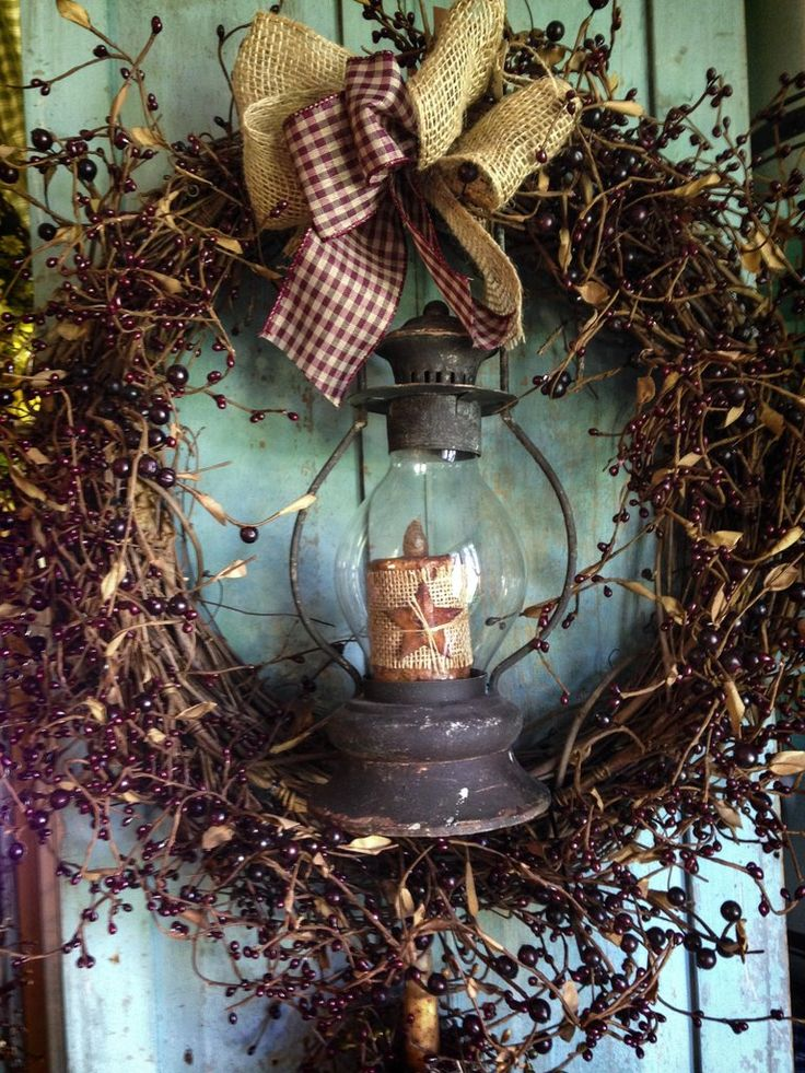 """This wreath measures 20"""" in diameter and features a 16"""" rustic lantern with timer candle. The candle is decorated with burlap and a small rusty star. The burgundy pip berries with a burlap and gingham"""