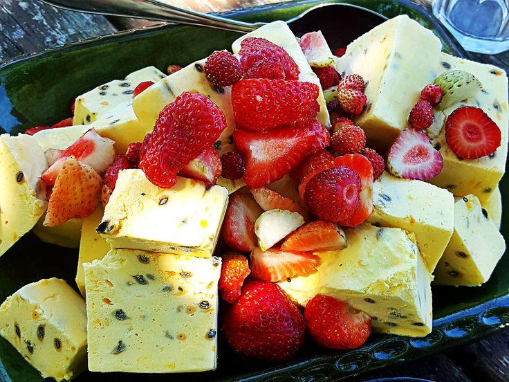 Hemgjord passionsfruktsglass på ett fat tillsammans med jordgubbar, smultron och chokladsås.