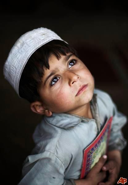 An Afghan refugee boy looks up as he waits for his daily lesson on how to read verses of the Quran, Islam's Holy book, at a mosque in a poor neighborhood of Rawalpindi, Pakistan, Tuesday, Jan. 19, 2010.