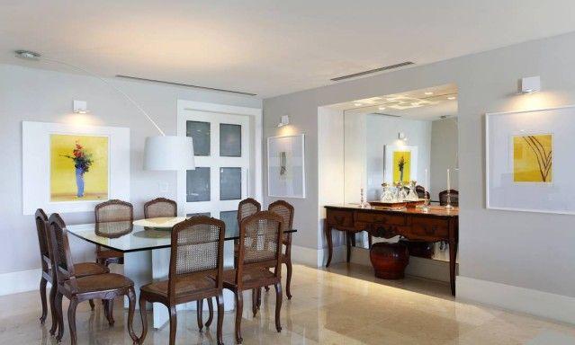 Sala de jantar ganhou base em tons neutros para receber bem aparador e cadeiras francesas, herdados pela dona do imóvel na Barra