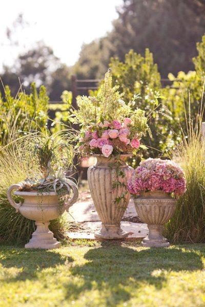 Macetas y canteros de jardín repletos de flores en remplazo de los arreglos florales. Buenas Ideas para Decoraciones Exteriores en Bodas. Imagen: Style Me Pretty