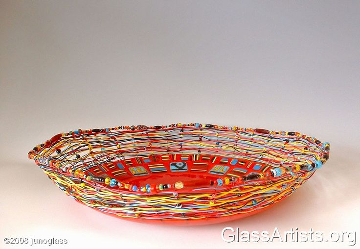 """Wire is fused into a red glass base, and then woven with recycled telephone wire and beads. The beads are a combination of trade, vintage and other glass beads. This piece is about 16"""" wide and 3"""" tall."""