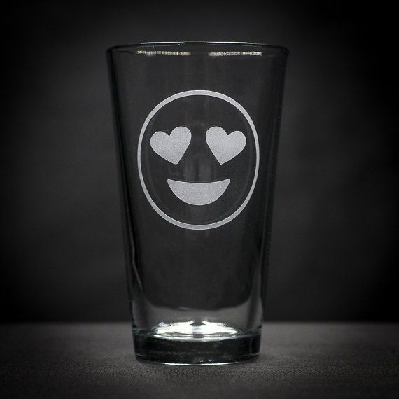 Heart eyes emoji glass. Used as an expression of love, this adorable emoji has hearts for eyes. Usually used to say I love you or I love this - this expressive face shows unbridled joy! Weve taken our version of the heart eyes emoji and sand carved it into this pub glass. Sand carving is a permanent process, with deep etching into the glass - this is not vinyl or paint and is a permanent process. This will not fade, even with repeated dishwasher cleaning. And unlike laser engraving, there is…