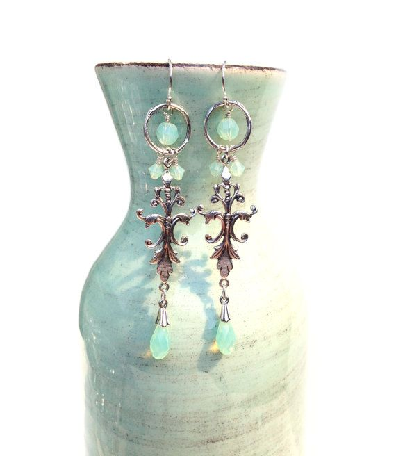 I love the color of these earrings. They are minty, semi-transparent, reflective swarovski crystals that are so lovely in the light, the photos dont do them justice. The overall design is ornate, which is great for a special occasion or to add a pop of colour and to dress up an understated outfit. Matching necklace available: https://www.etsy.com/listing/400423285  Materials: Sterling silver and swarovski crystals  Dimensions: Length without ear hook - 2 3/4 inches Length including ear hook…