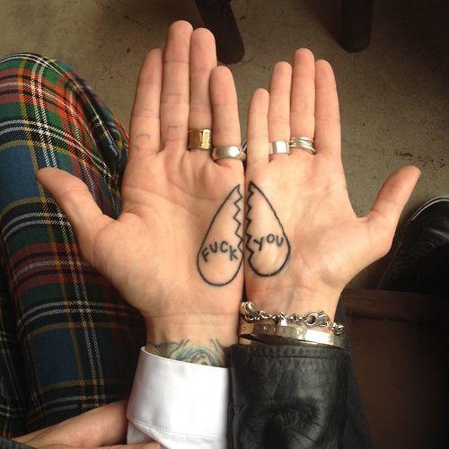 """Pequeño tatuaje en la palma de la mano de un corazón roto que dice """"que te jodan""""."""