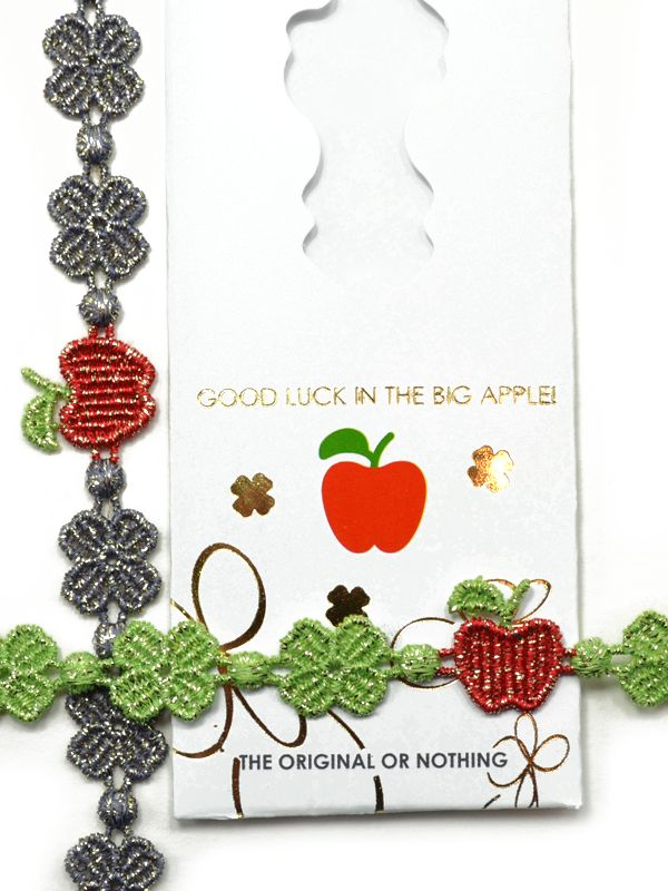 """The Big Apple: adorable apple surrounded by signature clovers Various colors, solid and lurex styles Comes with special Cruciani case Size Adult - 9 3/4"""" total length Made in Italy by Cruciani Macrame lace"""