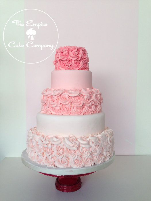 Wedding cake- Five circle tiers -pink ombre  coloring - top layer is dark pink buttercrem roses -second and fourth layer are smooth while the top, third, and fifth tier are buttercream roses