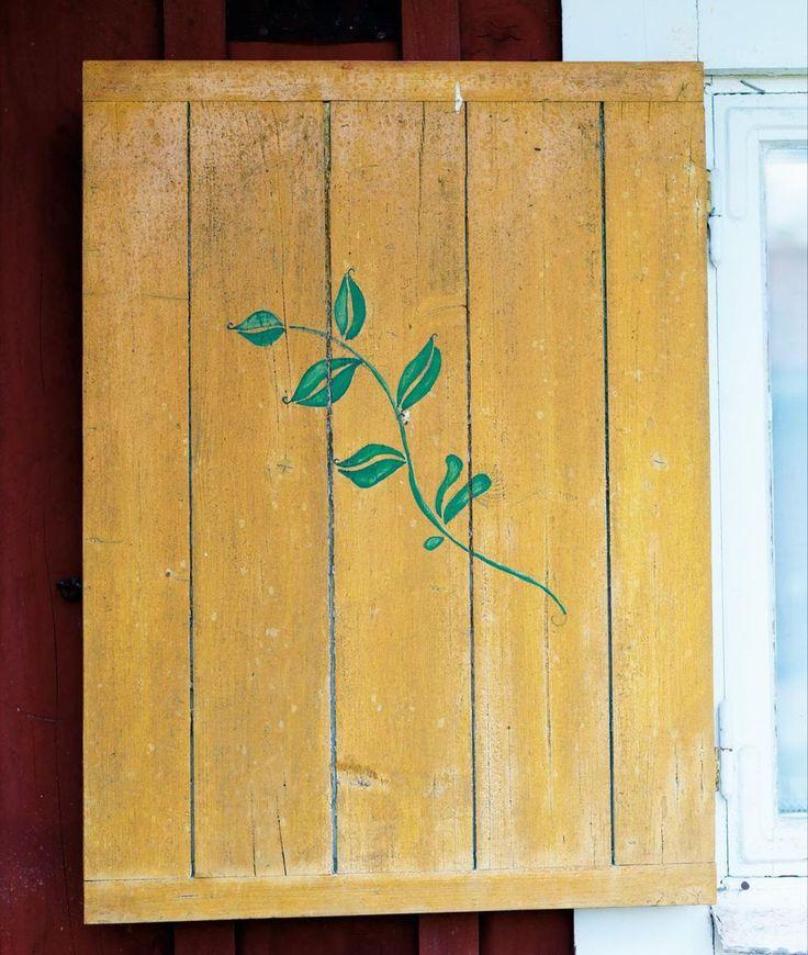 Mary Lou har målat en av torpets fönsterluckor.