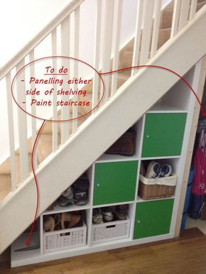 Home office supplies are stored under a staircase in a basket, a trolley,  and