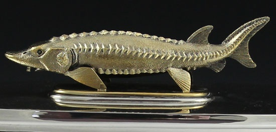 An unusual and one of a kind sterling silver caviar container by Asprey of Bond Street hallmarked 1978, London. The oval base has four applied cast dolphin feet and two hinged cast shell form handles that raise for lifting. The pull off lid has a detailed sturgeon as the finial. The liner is heavily gilded and pulls out. Matching spoon clips into the lid for storage.
