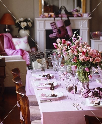 Vases of pale pink tulips and roses are used as a centrepiece on a laid table with little lanterns for place settings